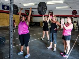 a woman holds a heavy barbell overhead in a crossfit gym while several other women behind