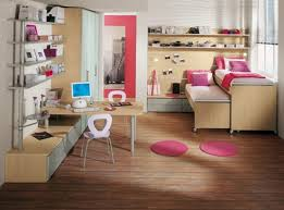 minimalist kids bedroom with pink bed wooden storage and woodedn desk with wooden floor and small round rug image