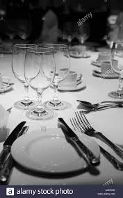 glasses table setting. Dinner Table Setting Including A Knife Fork Spoon Plate And Glasses On White Cloth With Upright Napkins In Black C