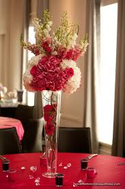 centerpiece with hydrangea stock and roses up top and inside clear glass vase are roses