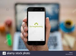 A Man Looks At His Iphone Which Displays The Survey Monkey Logo