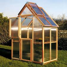 glass greenhouse natural wood frame on grass