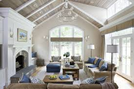 vaulted living room in white wall and ceiling beige sofa blue pillow blue