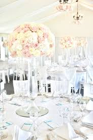 luxury blush pink and white wedding flowers and cake at hunton park peony hydrangeas and roses tall vase centrepieces with crystals and fl chandelier