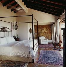This spanish styled bedroom shows a neutral color scheme, shows lines in  the bed and pattern on the tile flooring and carpet.