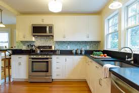 decorative green backsplash and white cabinets with black countertop for open kitchen design ideas using minimalist ceiling lights