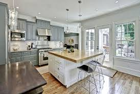 Traditional kitchen with gray cabinets, white island, white subway tile and  wood countertops