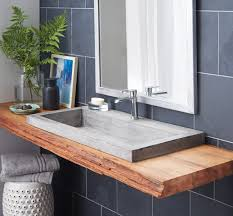 bathroom rectangle grey concrete sink and steel faucet with brown wooden base floating on grey