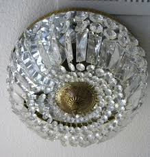 it is a flush mount gold and crystal light fixture that holds three light bulbs and has a mirrored top it puts off such pretty and bright light