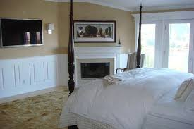 Classic Raised Panel Wainscoting with fireplace mantel in a Bedroom.