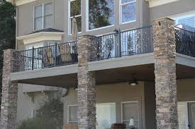 wonderful wrought iron balcony railing fence exposed stone pillars grey painted wall outdoor patio seating