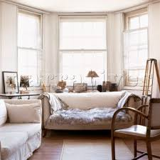 Double glazed bay window setting with sofa and fur throw and African  objects on display
