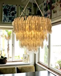 image above all you need is wax paper ribbon and a hanging planter basket and you have a capiz shell chandelier from brenna s paper capiz shell chandelier