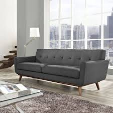 living room suprising grey fabric couch with back and arms also brown wooden legs on