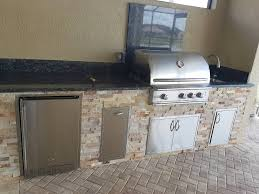 elegant outdoor kitchen with blue sapphire granite and golden white stacked stone