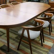 1950 60s teak dining table with 3 leaves from famed danish retailer illum boghus in the style of kai kristiansen shown with set of 6 teak chairs from