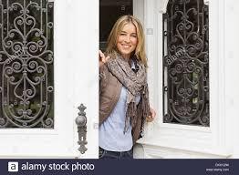 opening front door. Mid Adult Woman Opening Front Door - Stock Image