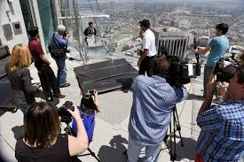 members of the news media record a fellow member riding the skyslide from the 70th to