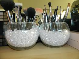 use a fishbowl fill it with colorful pebbles as a holder for your makeup brushes