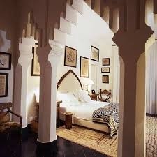 arabian asian style master bedroom with wall hanging pictures and area rug and calligraphy blanket