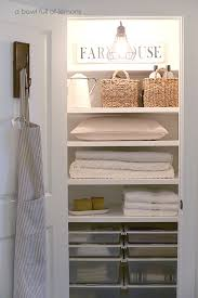 i love the sign and light and hook on the door in this farmhouse linen closet via a bowl full of lemons plus those pullout bins would be perfect for