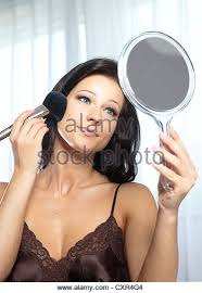 woman holding hand mirror. Young Woman At A Dressing Table Holding Hand Mirror And Powder Brush - Stock