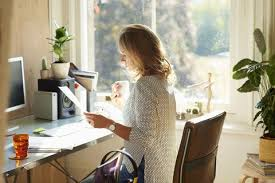 healthy home office. Woman Drinking Coffee And Reading Paperwork At Desk In Sunny Home Office. Healthy Office