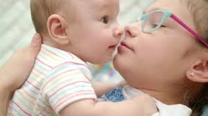 happy sister kissing baby brother