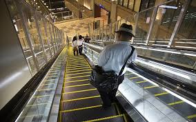 people on escalators. travellers stand on the right of escalator in osaka station people escalators k