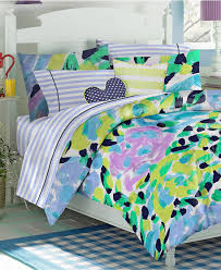 green purple yellow and blue pattern bedding bed on white wooden bed