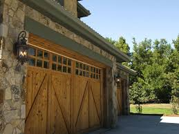 home garage door rustic look of this home is amplified by natural wood garage doors featuring upper panel windows xfinity home security garage door