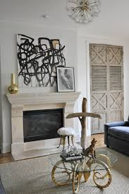 modern french living room with abstract canvas art over stone fireplace antique folding doors diamond jute rug and antique brass glass top tail table