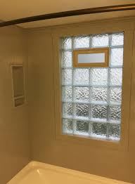 a glass block wave pattern vented window with solid surface trim for a watertight shower window