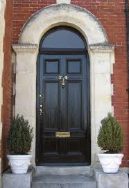 rustic entry doors for home. an old fashioned, rustic style black front door on this red brick home is framed entry doors for