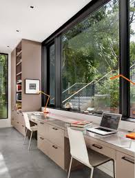 home office images. The Light Colored Cabinets, Shelves, And Desk For Two, Is Built Into Wall Of This Modern Office. Facing A Large Black Framed Window, Work Space Home Office Images