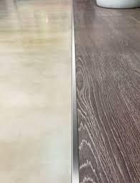 Terminacin cuadrada de acero que une pisos de porcelanato y revestimiento  de madera.