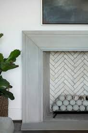 beneath a framed tv niche a gray beveled mantel frames a fireplace fitted with an ivory herringbone firebox and concrete fire