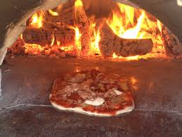 a photo of a pizza cooking in our homemade wood fired pizza oven