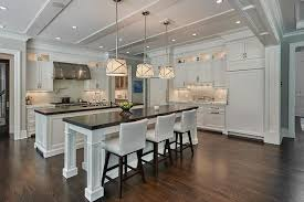 side by side white kitchen islands with honed black marble countertops