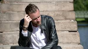 a young and attractive man in his 20s sitting down outside on a set of steps wearing a white shirt black jeans with a black leather jacket