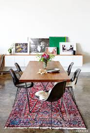 an industrial and modern dining e with leaning artwork persian rug and wood dining table