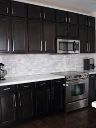 Dark Birch kitchen cabinets with Shining White Quartz counters and White  Marble backsplash:  Grey Subway TilesWhite ...