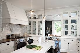 traditional white kitchen cabinets rounded glass pendant light stainless steel range gas oven cooking pots marble dining table black chairs square cutting