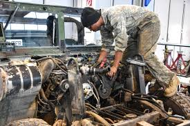 a solr performs maintenance on a humvee vehicle engine