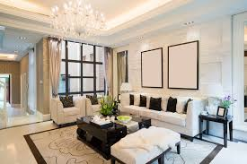 Luxury home living room with tray ceiling, white couches, and chandelier