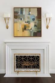 earth toned abstract art with white fireplace mantel
