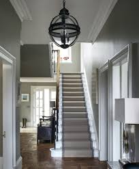 Traditional hallway with parquet flooring, stair runner and statement  pendant light