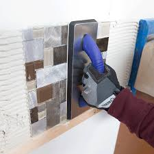pressing tile backsplash into the thinset with a tile float with tile over sheetrock