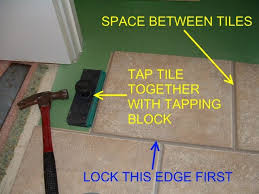 laminate flooring laying over concrete source quick step tile being tapped together with a tapping block