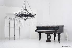 light room with a piano a folding screen and a chandelier